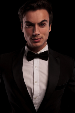 male face: serious sexy man in tuxedo posing for the camera on black studio background Stock Photo