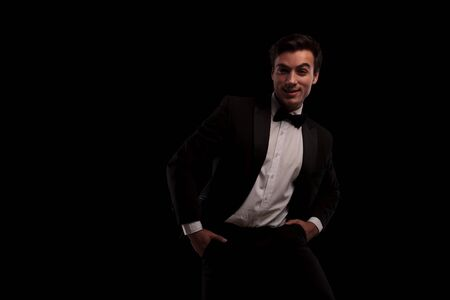 smiling young elegant man in tuxedo and bowtie standing with hands in pockets on black background Stock Photo