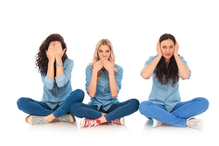 three young women making the no evil poses sitting on white background Stock Photo