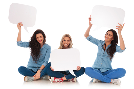 mujeres sentadas: three seated young women smile and hold blank speech bubbles on white background Foto de archivo