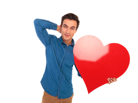 big behind: relaxed casual man holding big red heart with hand behind his neck posing on white background Stock Photo
