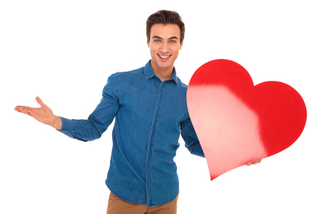 big shirt: happy young casual man welcoming you to valentines day by holding a bif red heart in his hand