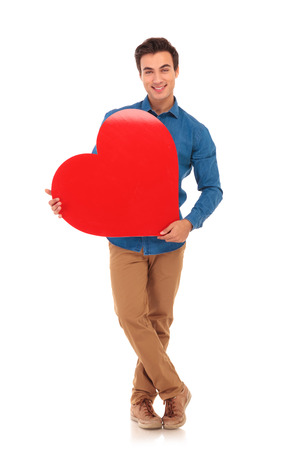 hold on: full body picture of a young happy man holding a big heart on white background Stock Photo