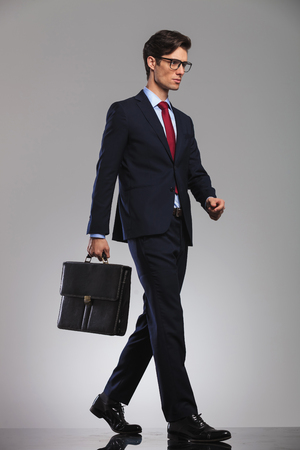 young businessman wearing glasses and suitcase is walking, side picture in studio Stock Photo