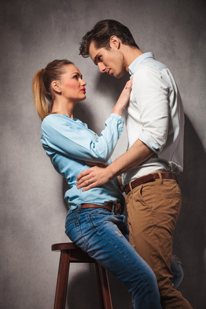 hold hands: in love couple , woman sitting and man standing and look at eachother in studio Stock Photo