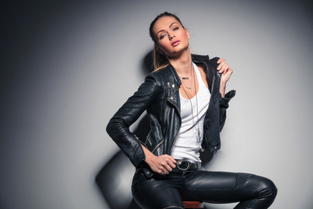 attractive blonde woman in leather clothes sitting and posing for the camera in studio
