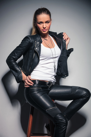 seated sexy woman in leather clothes is holding her coat by collar and one hand on waist Stock Photo