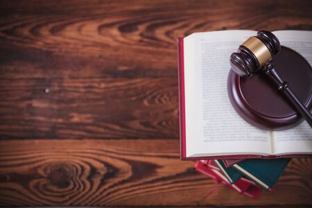 picture of a judges gavel on top of pile of books on wooden backround with copy space