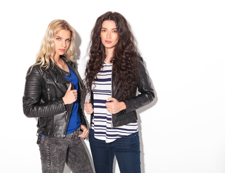 two serious young women in leather jackets holding their collars and look at the camera