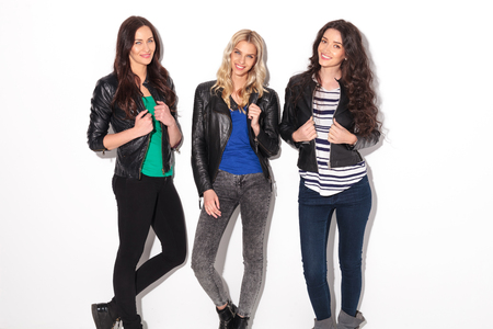 smiling casual women in leather jackets standing against white studio wall
