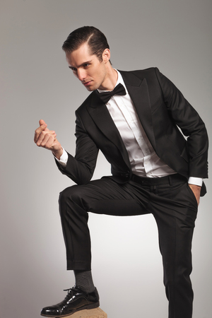 young businessman in tuxedo snapping finger and looks away to side on grey background