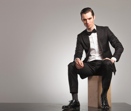 man sit: young man in tuxedo is sitting with open coat on grey studio background