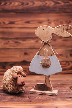 textured wall: female wooden bunny near sheep on old wood background