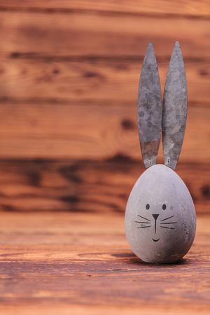rabbit standing: cute easter egg with rabbit ears and copyspace on old wood background