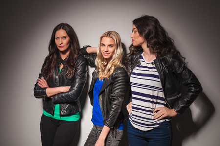 mani incrociate: three young casual women in leather jackets posing in studio