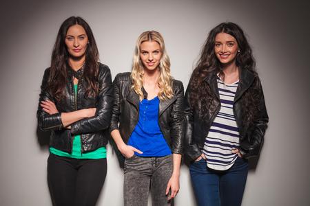 Drie gelukkige vrouwen in leren jassen glimlachen naar de camera in de studio