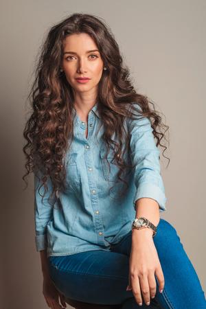 belle brune: Femme souriante aux cheveux bouclés assise sur chaise en studio sur fond gris
