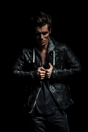 angry man pulling his leather jackets collar on black studio background