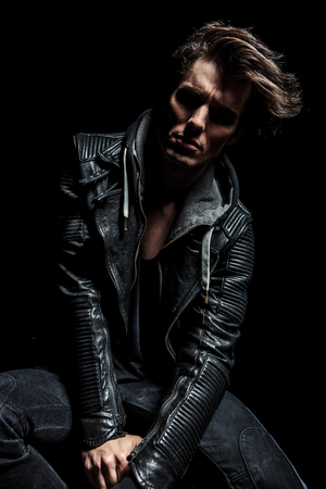 stool: dramatic man with messy hairstyle sitting on chair on black background, wearing leather jacket Stock Photo
