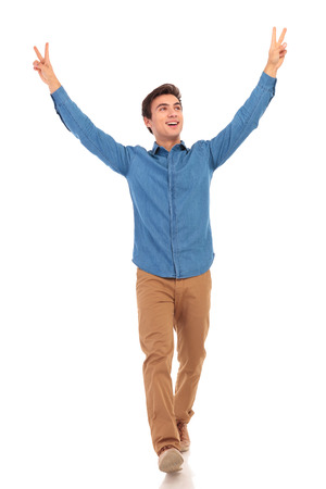 casual man walking with hands up in the air and looks to side, making victory or peace sign, on white background Stock Photo