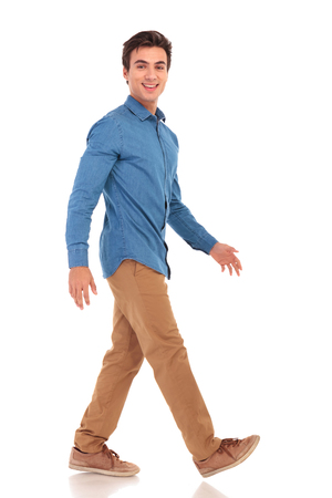 zijaanzicht van een lopende lachende toevallige man op witte studio achtergrond