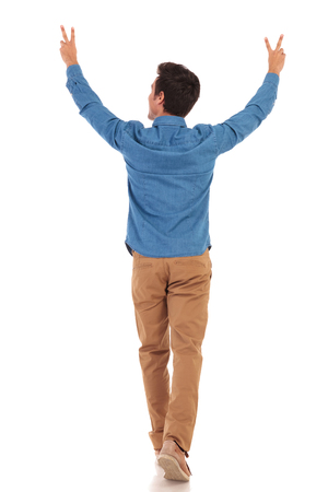 back view of a casual man walking with hands in the air making the victory sign on white background