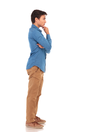 looking away from camera: full body picture of a pensive casual man looking away from the camera on white background