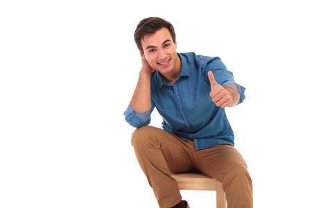 relaxed seated casual man making the ok thumbs up hand sign on white background
