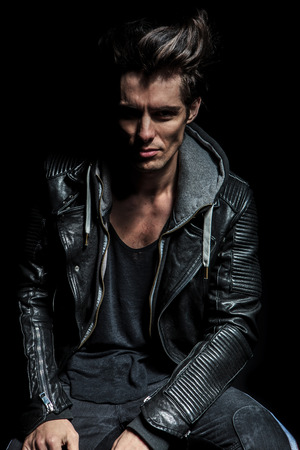 stool: portrait of a punk in leather jacket on black background