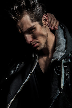 closeup picture of a man holding hand behind his neck, wearing leather jacket on black background
