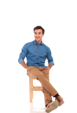 full body picture of a relaxed seated man looking to side on white background