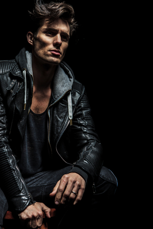 stool: seated man in leather jacket dreaming away on dark background