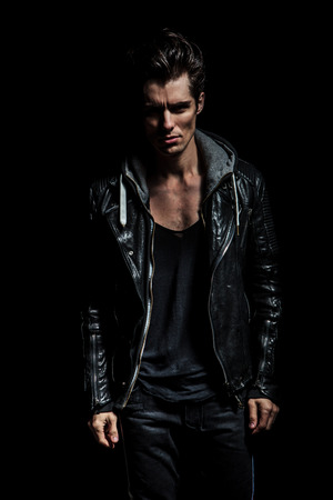 young male: dramatic portrait of a young man in leather jacket standing on black background