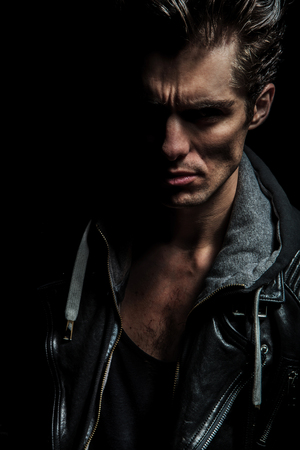 closeup portrait of a dramatic man in leather jacket on black background Stock Photo