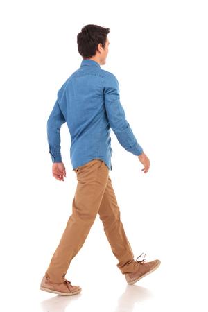白い背景の上歩く若いカジュアルな人の後ろ側ビュー