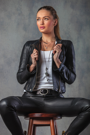 side view of young woman holding leather jacket's collar and looks away from the camera photo