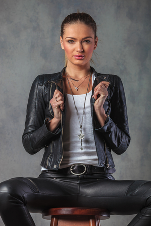 stool: sexy young blond woman in leather jacket pulling collar while sitting on stool