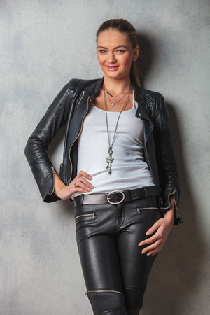 smiling young woman in leather clothes posing for the camera with hand on waist in studio photo