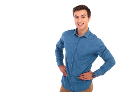 happy casual man with hands on hips smiles for the camera on white background