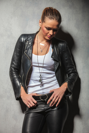 sexy blonde woman in leather clothes looking down while posing in studio photo