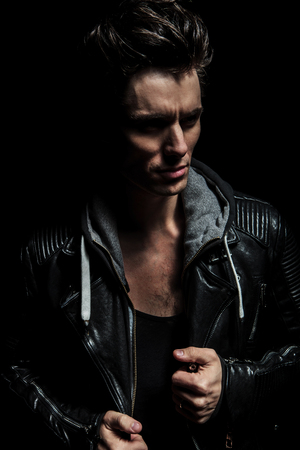 side view portrait of a dramatic man in leather jacket on black background photo