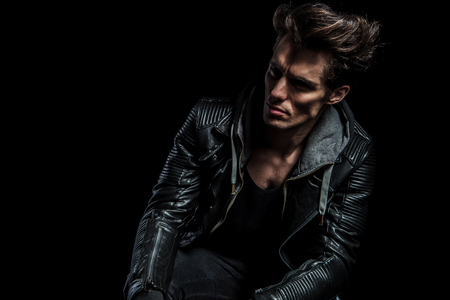 dramatic portrait of a fashion model in leather jacket looking away to a side on black backgroud photo