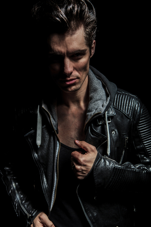 serious portrait of a young man in leather jacket on dark studio background photo