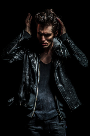 cool man in leather jacket fixing his hairstyle on black background photo