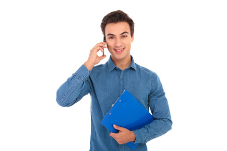 young man holding clipboard and talks on the phone on white background
