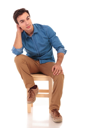 full body picture of a seated casual man dreaming away on white background Stock Photo