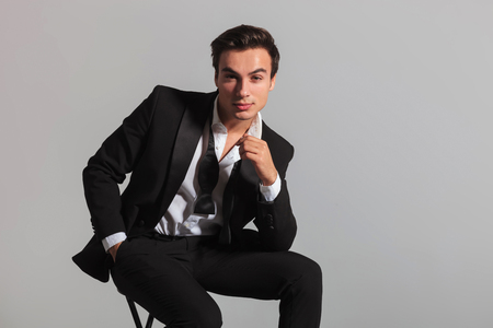 elegant man in tuxedo is sitting and thinking holding his chin