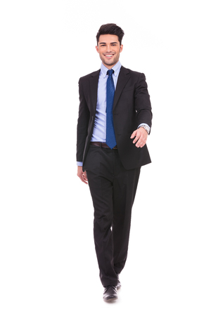 happy young businessman walking forward on white background photo