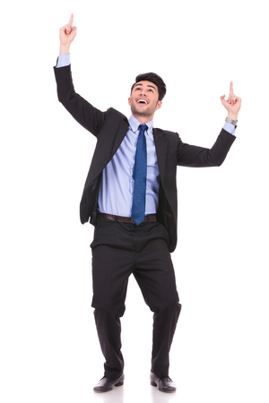full body picture of an excited businessman pointing fingers and looking up on white background photo