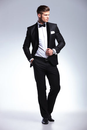 full length picture of an elegant young fashion man in tuxedo holding his hand om his jacket while looking away. on gray background photo